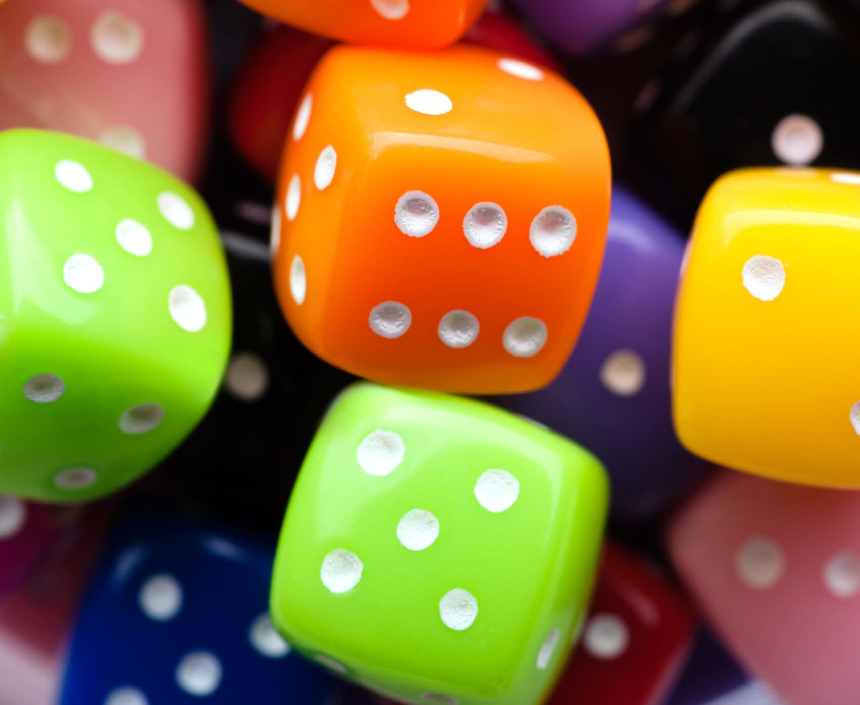 Assorted multicolor dices, close-up shot, abstract gambling background